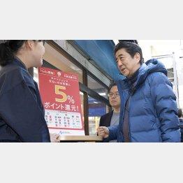 キャッシュレス体験で商店街の鮮魚店を訪れた安倍首相(C)共同通信社