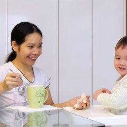 赤ちゃんに朝食を食べさせるフィリピン人家政婦(シンガポール)