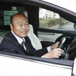 スーツを着込んで車に乗る佐野慈紀さん