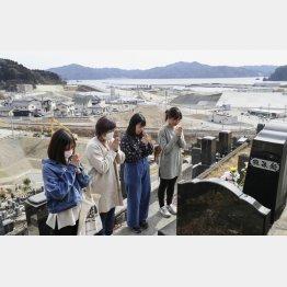 震災から8年になる前日、岩手県大槌町の高台にあるお墓を訪れ手を合わせる親子(C)共同通信社
