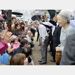 安倍首相とは正反対の天皇陛下(福島市内の復興公営住宅を視察され、集まった住民に声をかける天皇、皇后両陛下)/(C)共同通信社