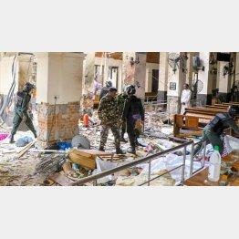 爆発が起きた教会の内部を調べる治安要員(C)ゲッティ=共同