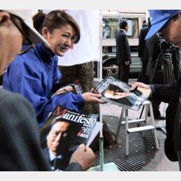 街頭演説会場で配られるマニフェストの冊子を手にする有権者たち(C)共同通信社