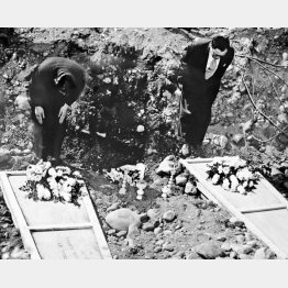 アッツ島で、埋められる火葬の残灰に拝礼をする江間(左)、稲田両事務官=1953(昭和28)年7月/(C)共同通信社
