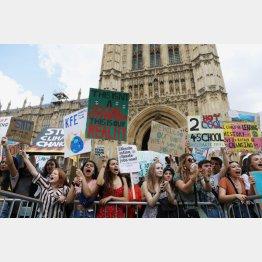 ロンドンの国会議事堂前で行われた温暖化対策を求めるデモで、プラカードを掲げる参加者ら(C)ロイター・共同