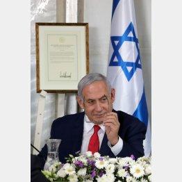 ゴラン高原の閣議に臨むネタニヤフ首相。後方には「ゴラン高原はイスラエル主権下」とトランプ米大統領の承認証が/(C)ロイター