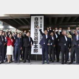 選挙本部の看板前で気勢を上げる安倍首相(中央右)ら(C)共同通信社