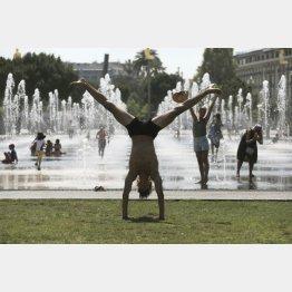 噴水で涼を取る人々(C)ロイター