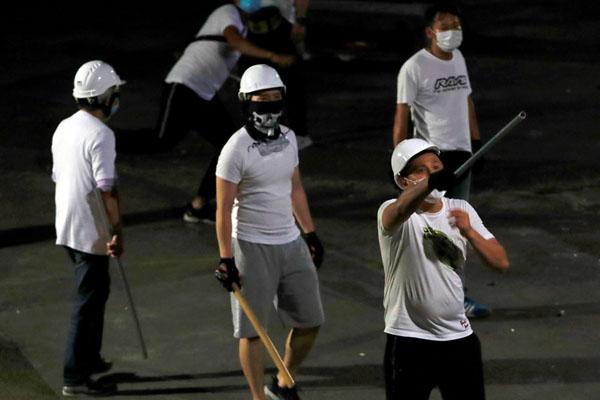 襲撃後、こん棒を手に元朗駅に留まる白シャツ集団の男ら(C)ロイター