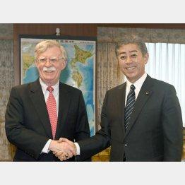 7月22日、ボルトン米大統領補佐官(左)と握手を交わす岩屋防衛相(C)共同通信社