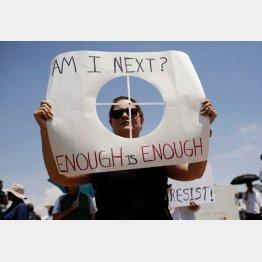 プラカードを掲げて抗議する女性(C)ロイター