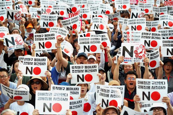 「安倍政権を糾弾する」と書かれたプラカードを手に抗議する韓国国民(C)ロイター