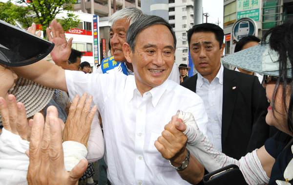 後ろの青島候補より「令和おじさん」(菅官房長官=央)が人気/(C)日刊ゲンダイ