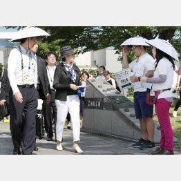 テスト大会で傘をかぶって活動するボランティア(右2人、視察に訪れた小池都知事=左2)/(C)共同通信社