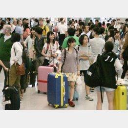 帰国した人たちで混雑する成田空港(C)共同通信社