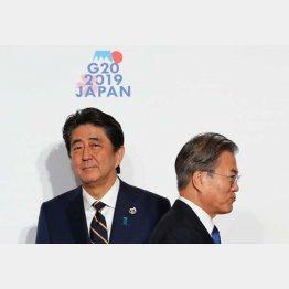 G20大阪サミットで握手した後、すれ違う韓国の文在寅大統領(右)と安倍首相(C)ロイター