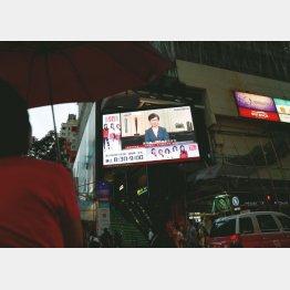 街頭のスクリーンに映し出されたニュースを見る人々(C)ロイター