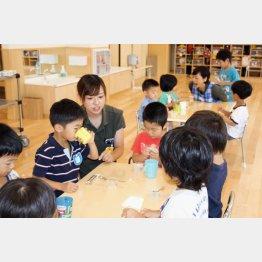 私立保育所でおやつを食べる子どもたち(C)共同通信社