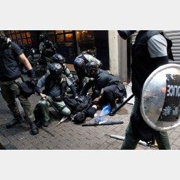 デモ参加者を拘束する警察官ら(C)ロイター