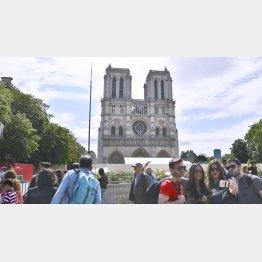 パリは多くの人が訪れるが…(ノートルダム寺院前で記念撮影する観光客)/(C)共同通信社