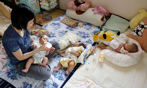 三つ子の赤ちゃんにミルクを飲ませるお母さん。3人同時に与えるために、ほ乳瓶をタオルで支えるなど工夫をこらすが、過酷な育児環境が現実だ(C)共同通信社