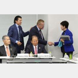 合同会議で握手するコーツ調整委員長と小池知事(左は組織委の森会長)/(C)共同通信社