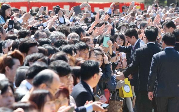 「桜を見る会」で次々に招待客とハイタッチをしてまわる安倍首相(C)日刊ゲンダイ