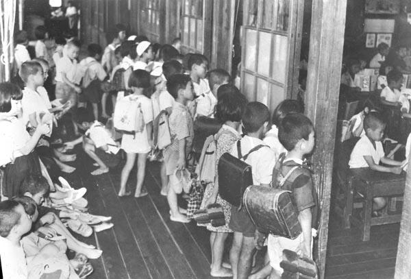 教室が足りない学校では午前と午後の2部授業を実施、廊下で教室が空くのを待つのが日常風景。宮城県仙台市立八幡小学校で(1953年5月4日)/(C)共同通信社