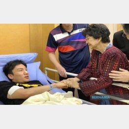 事故で顔を負傷し、病院でマレーシア首相夫人から見舞いを受ける桃田(左)/(C)ベルナマ通信提供=共同