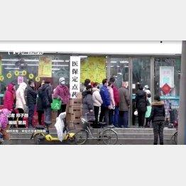 中国・武漢市で、マスクを着け処方箋薬局に列を作り並ぶ人たち(C)ロイター/中国通信社
