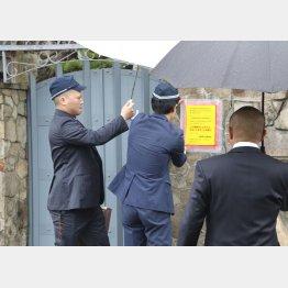 1月7日、山口組総本部に「特定抗争指定暴力団」であることを示す標章を張り付ける兵庫県警の警察官(右は、立ち会いの組関係者)/(C)共同通信社