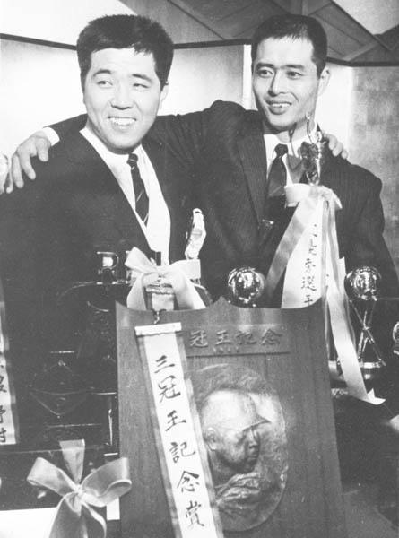 プロ野球両リーグ・個人タイトル表彰式で肩を組む巨人・王貞治と南海・野村克也両選手。入団12年目の野村は戦後初の三冠王を獲得、7年目の王は本塁打と打点がトップで、共にリーグMVPに選ばれた=1965年11月(C)共同通信社