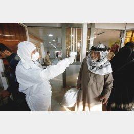 イランとイラクの国境ゲートで乗客の体温をチェックするイラクの医療スタッフ(C)ロイター/Essam al-Sudani