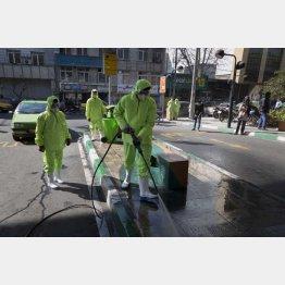イランの首都テヘランで街中を消毒して回る防護服の消防隊員ら(C)ロイター