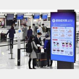 成田空港には感染症対策を呼びかけるモニターも(C)共同通信社