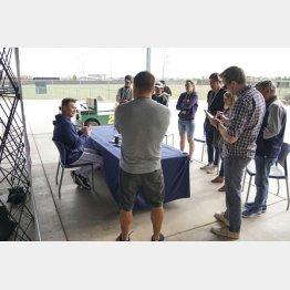 新型コロナウイルスの感染拡大防止策で、監督室の外で記者会見するマリナーズのサービス監督(左)=10日、ピオリア(C)共同通信社