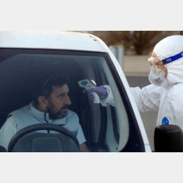 どう見てもパンデミック(スロベニアとイタリアの国境でコロナウイルスのチェックをする作業員)/(C)ロイター