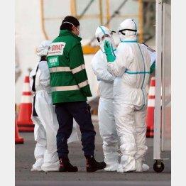 ダイヤモンド・プリンセス号周辺で、防護服を着用し作業する関係者(C)日刊ゲンダイ