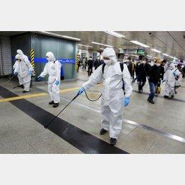ソウルの地下鉄駅構内を消毒する関係者(C)ロイター=共同