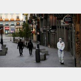人影が消えたマドリード市街の通りを歩く警官と防護服の医療関係者(C)ロイター