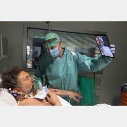 イタリア北部ブレシアの病院の集中治療室で、テレビ電話で親族と話す患者のためタブレット端末を持つ医者(Sergio Cattaneo/Brescia/Spedali Civili提供、AP=共同)