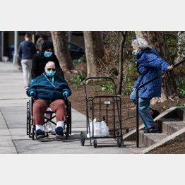 どう安全対策して高齢者を守るのかが緊急課題に(自粛体制で人通りの少ない通りに出る人たち=ニューヨーク)/(C)Bildbyran