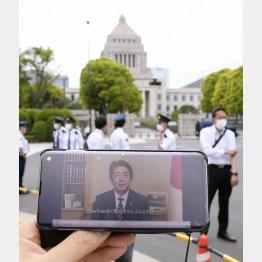 3日、スマートフォンの画面に映し出された、改憲派の会合に寄せられた安倍首相のビデオメッセージ。奥は国会議事堂(C)共同通信社