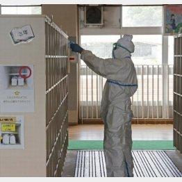 生徒の新型コロナウイルス感染が確認された中学校の校内を消毒する作業員(C)共同通信社
