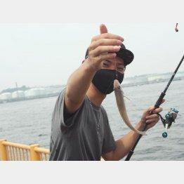 良型のシロギスが釣れて、マスクの上の目がニンマリ(磯子海づり施設で)/(C)日刊ゲンダイ