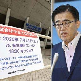 26日、J1名古屋で新型コロナウイルスの感染者3人が確認され、広島戦の中止を知らせる張り紙(右は会見する愛知県の大村知事)