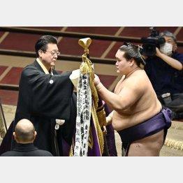伊勢ケ浜親方(左)から優勝旗を受け取る照ノ富士(C)共同通信社