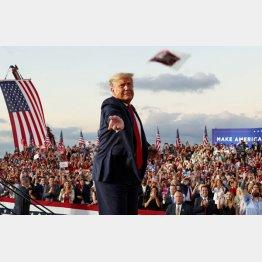 退院後、初の選挙演説地フロリダの集会で、群衆にマスクを投げて見せるトランプ米大統領(C)ロイター