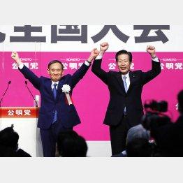 両手を上げる菅首相(左)と山口代表(27日、公明党の党大会で)/(C)共同通信社