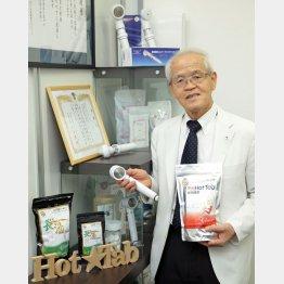 ホットタブと専用のシャワーヘッドを手にする小星重治社長(C)日刊ゲンダイ